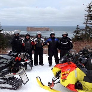 Snowmobile contest winners with Percé Rock in the background