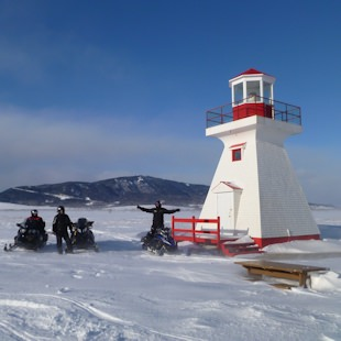 Snowmobilers at the Carleton Lighthouse in Gaspésie
