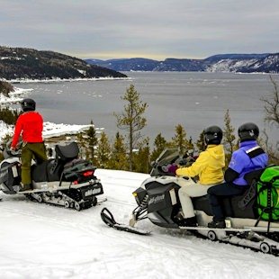 Snowmobilers with the Saguenay Fjord in the background