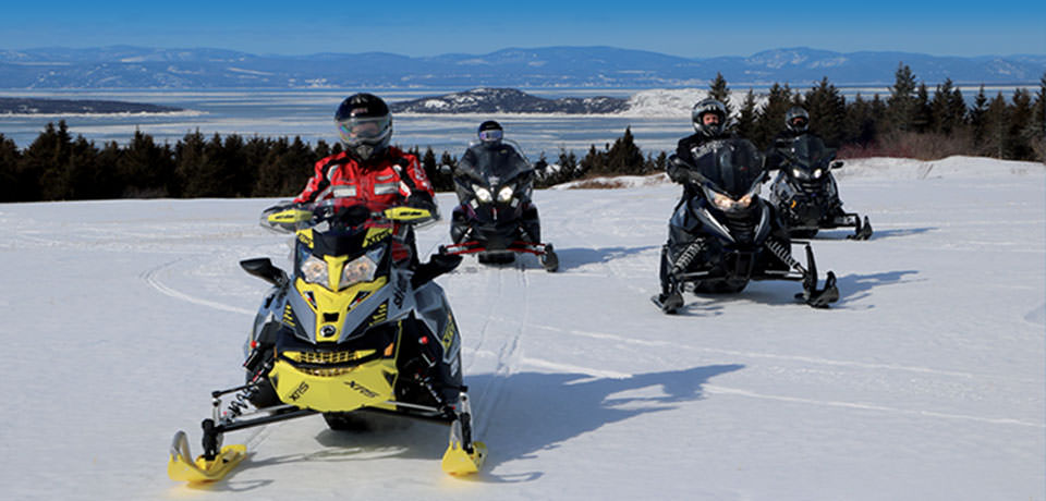 Snowmobilers with the St. Lawrence River in the background