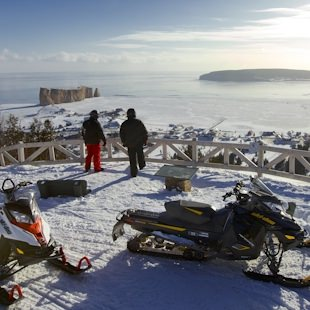 Snowmobilers enjoying a view of Percé Rock and Bonaventure Island